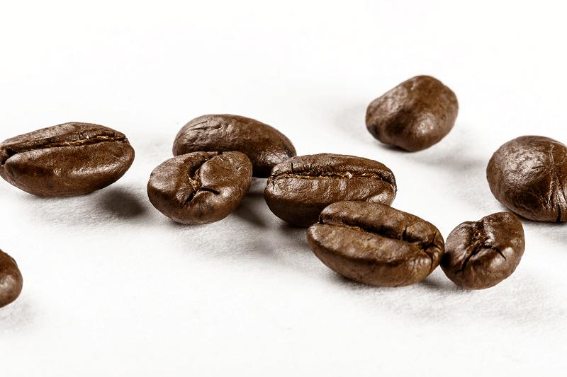 upražené kávové zrnká na bielom podklade