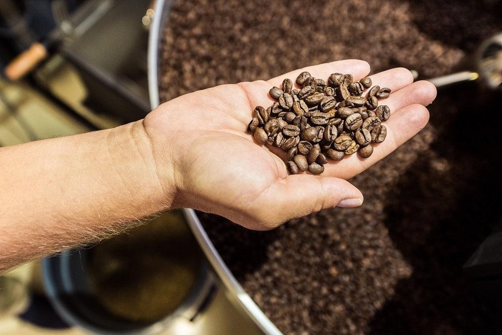 detail na ruku s upraženými kávovými zrnami