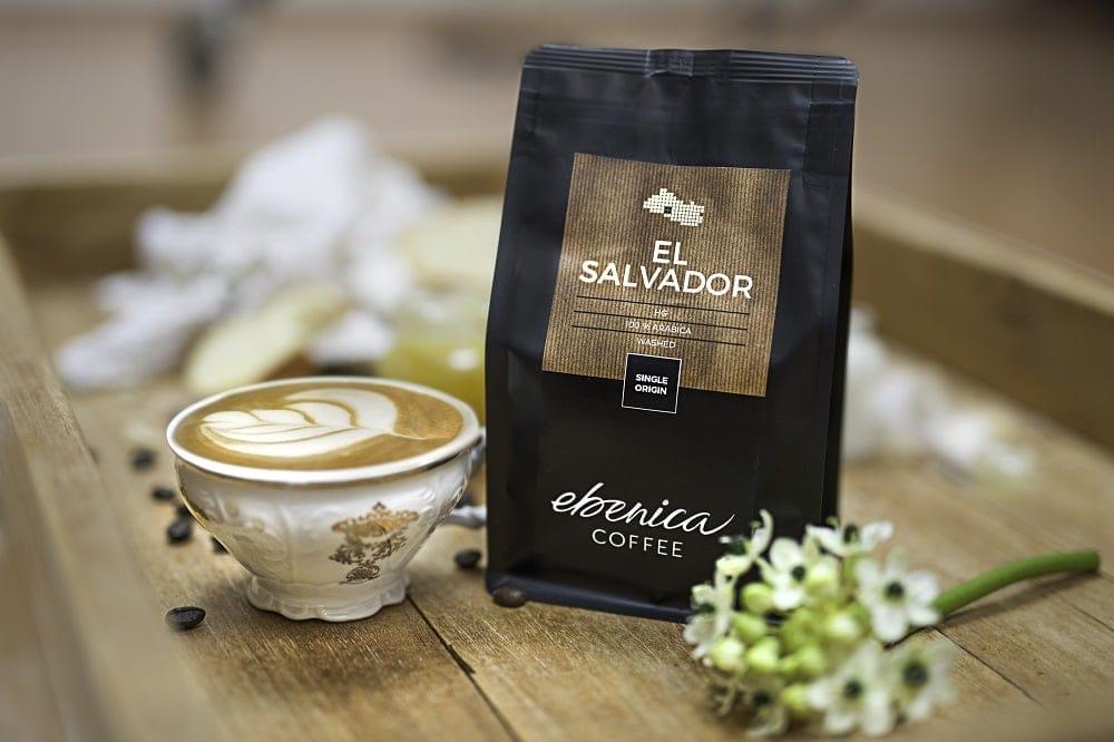 Šálka s cappuccinom a balíčkom kávy El Salvador