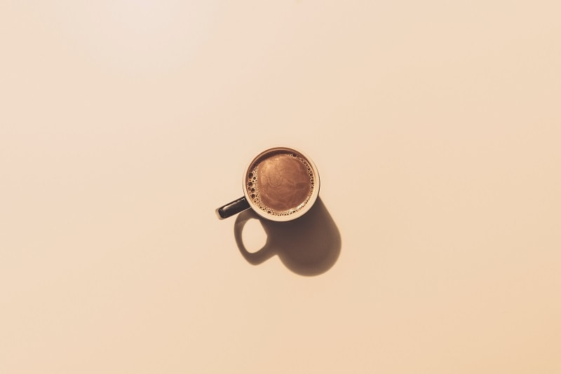 šálka kávy na ružovom podklade
