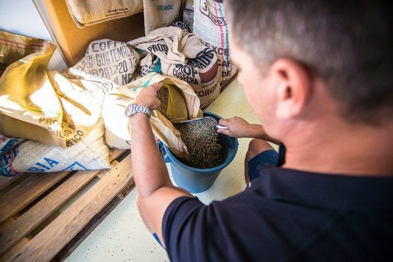 pražiar vyberá z vriec zelenú kávu
