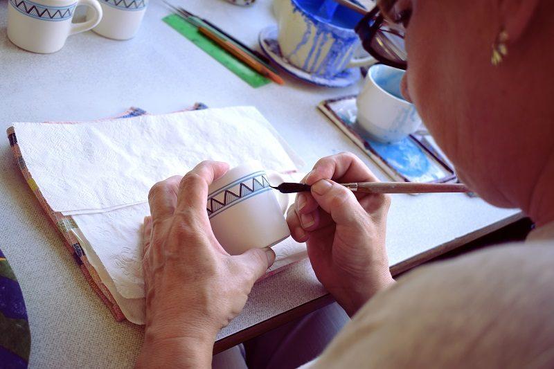 ľudová maliarka keramiky pri práci