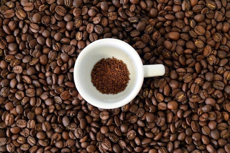 instantná káva v šálke položená na kávových zrnách