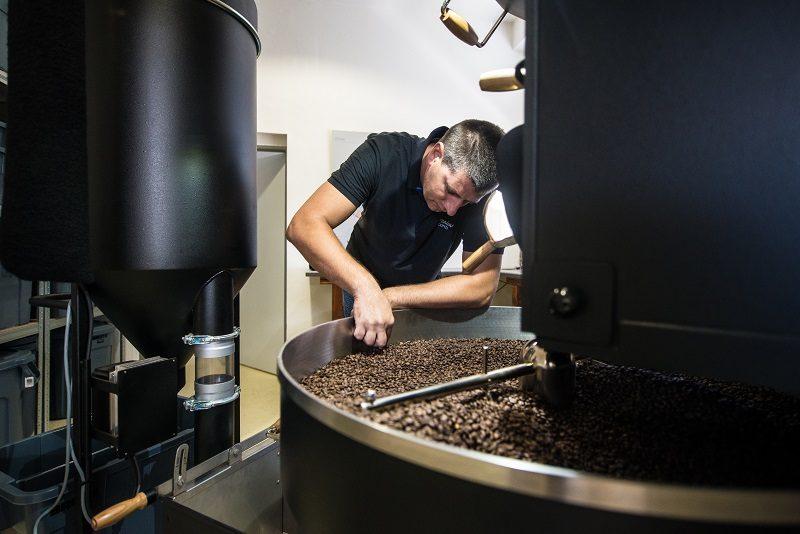 pražiar sa skláňa nad čerstvo upraženou kávou