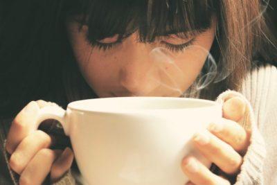tvár ženy nad šálkou kávy