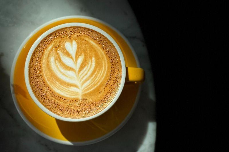 cappuccino v žltej šálke s podšálkou