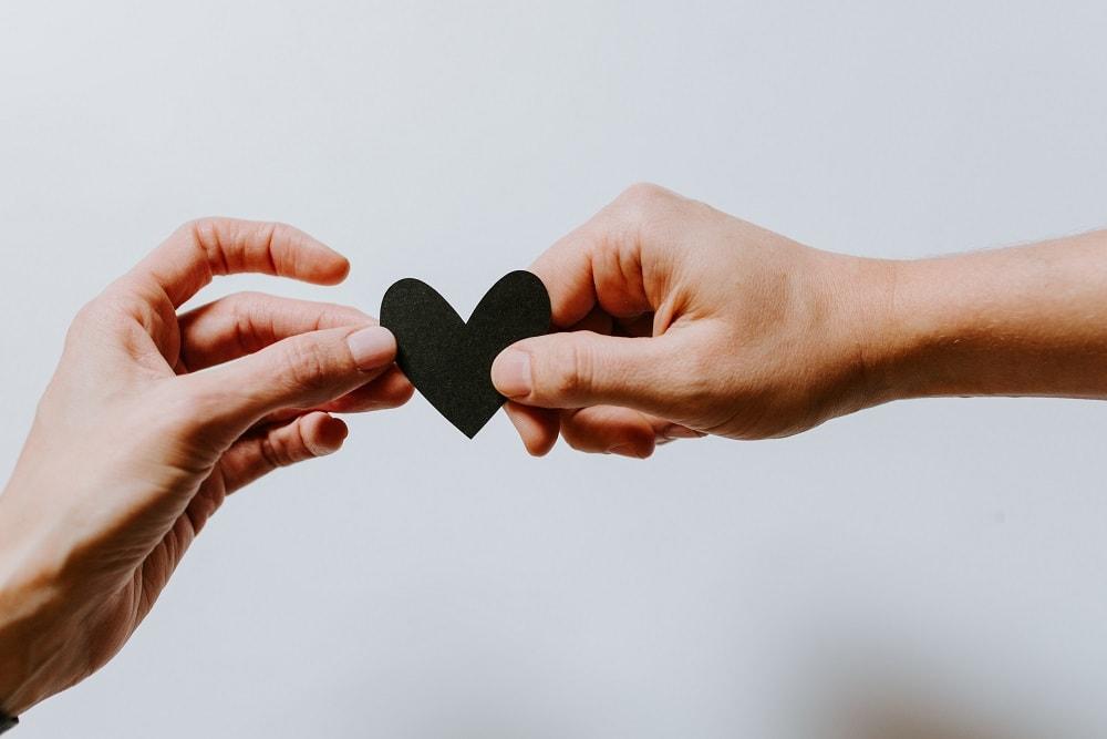 dve ruky držiace čierne papierové srdce
