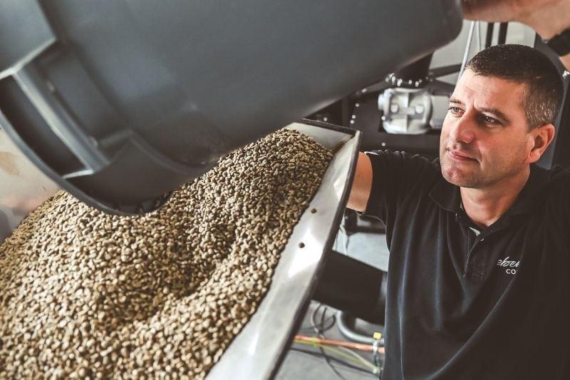 pražiar Andrej sype zelenú kávu do stroja